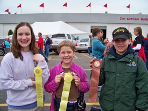 Sydney, Elaina, & Harrison Nobles flash their ribbons for the camera